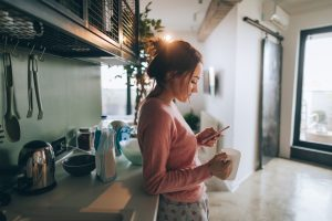 Young woman drinking first morning coffee and reading news in the kitchen of her apartment