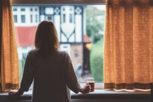 Rear view of woman at home looking out the window