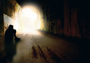 The silhouette of a teenage boy alone in a tunnel.